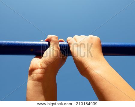 Hold On Bars At Playground. Kid Is Holding Blue Steel Bar Above Head
