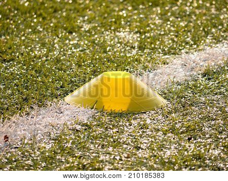 Bright Yellow Plastic Cone On White Line. Plastic Football Green Turf Playground With Grind Black Ru