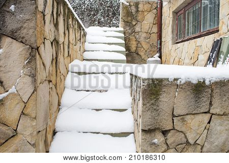Snow covered the stone stairs. Winter landscape.