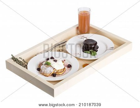 Pancakes with chocolate pudding and juice on a wooden tray with cutlery. Isolated on a white background.
