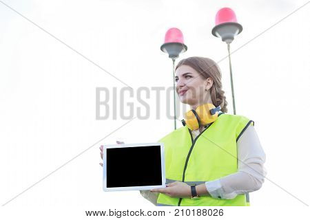 Young Pretty Woman In Green West And Earmuffs Stand On Roof And Show Empty Tablet