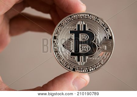 Man holds silver bitcoin in his left hand and appraise it. Close up. Blur background.