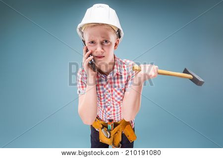Confused Construction Worker Talking On The Phone With A Hammer In His Hands