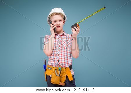 Portrait Of A Young Builder In A Helmet And A Tape Measure In His Hand