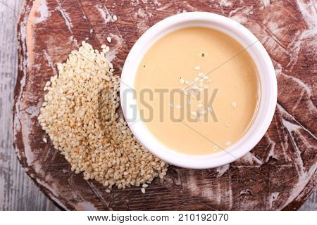 Tahini paste - sesame sauce on wooden board