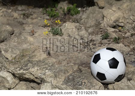 Football and the dark stone. Ball is situated on the rock.