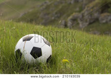 Football and the green hill. Ball is situated on the grass.
