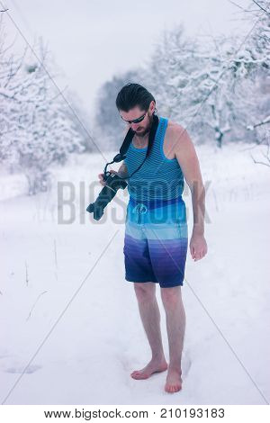 Naked Man With Camera Stand In The Winter Forest