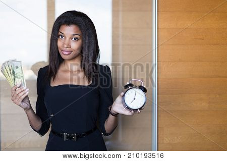 Pretty, Young Business Lady In Black Strong Suite Hold A Bundle Of Money And Alarm Clock