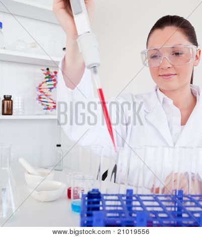 Cute female biologist holding a manual pipette with sample from test tubes in a lab