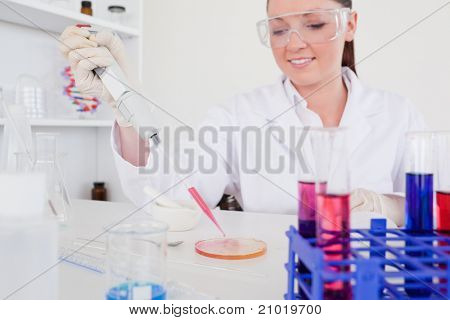 Pretty red-haired scientist using a pipette in a lab poster