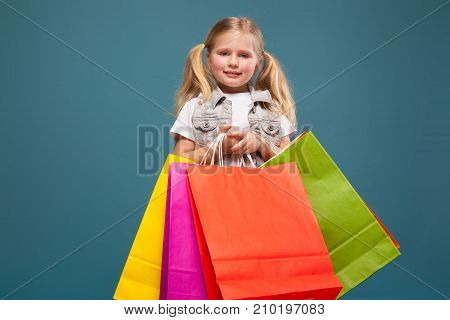 Adorable Cute Little Girl In White Shirt, White Jacket And White Shorts Hold Colorful Paper Bags