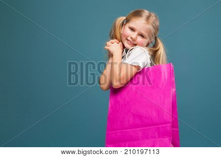 Adorable Cute Little Girl In White Shirt, White Jacket And White Shorts Hold Purple Paper Bag
