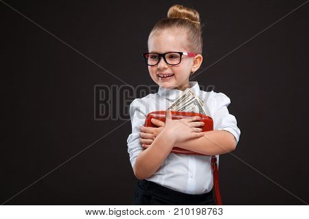 Pretty Cute Young Girl In White Shirt And Black Trousers Hold Red Purse With Money