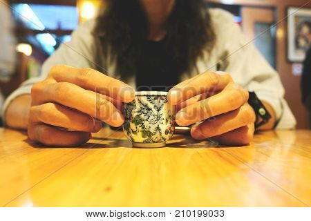 Woman holding a cup of hot tea and sitting at the table.