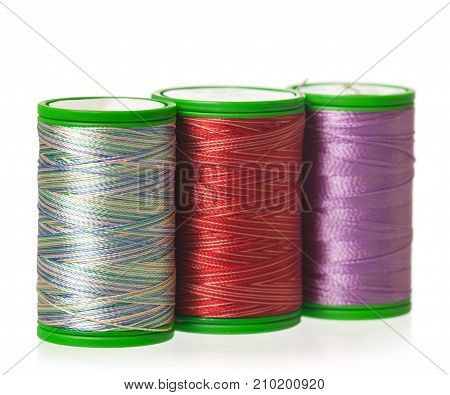 Colorful silk threads on a coils isolated on white background close-up