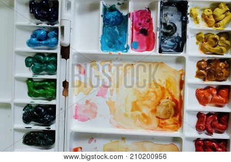 A closeup palate of water color paint on wooden black ground