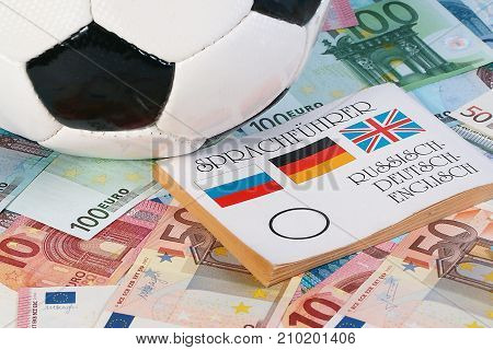 football leather ball and translator book lie on paper euro banknotes