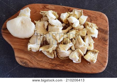 Fresh oyster mushrooms cut in big pieces on an olive wood cutting board on a grey abstract background. Step by step cooking