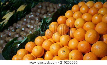 Fresh organic fruits (oranges kiwi bananas) on display in supermarket farmers market