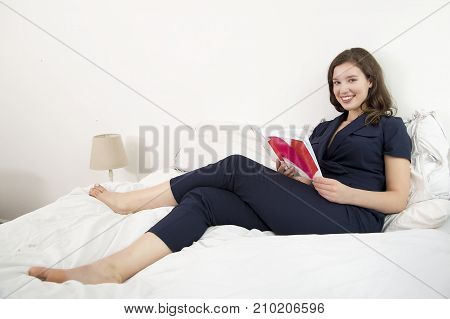 a young woman reading a book on her bed