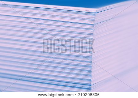 large stack of paper pages with sharp focus on the corner