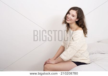 youung woman sitting on her bed looking happy