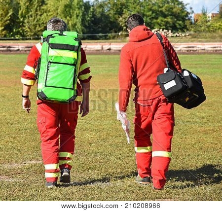 Ambulance staff with medical equipment on a sport track