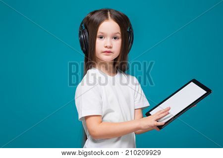 Beauty Little Girl In Tee Shirt And Earphones With Long Hair, With Tablet In Hands