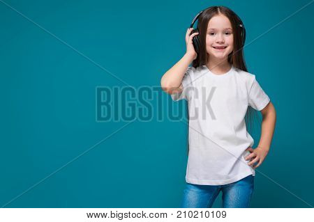 Beauty Little Girl In Tee Shirt And Earphones With Long Hair