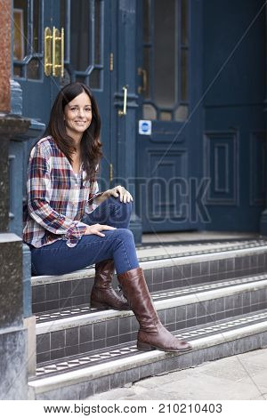 a young woman sitting on her doorstep