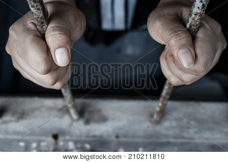 Prisoner with chain holding prison bar in jail
