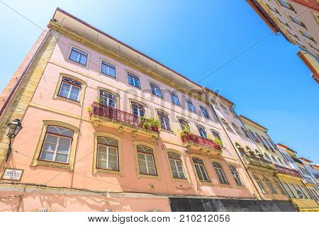 Coimbra, Portugal - August 14, 2017: windows architecture of historic buildings in Rua Ferreira Borges in center of Lower Coimbra, the medieval part of Portuguese city. Prospective view. Sunny day