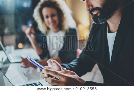 Bearded man using smartphone, holding in hands.Horizontal.Blurred background. Cropped