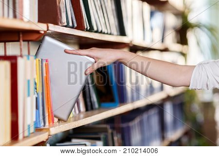 A top view on females hand picking up book from a library shelf. Many books on the shelves in the library. Close-up of book.