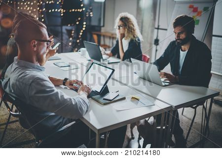 Group of young coworkers work together modern coworking studio.Young people making conversation with partners at the table.Horizontal.Blurred background