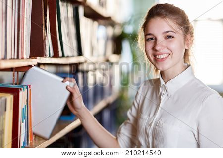 Portrait of clever student with book in college library. Beautiful girl posing on the camera and picking up book from shelves. Close-up of girl.