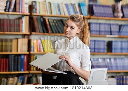 Beautiful young girl in a white blouse working with laptop in the library. Shelves with books on the background. Close-up of girl. Education concept.