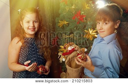 Happy little kids decorate Christmas tree in beautiful living room with traditional fire place.