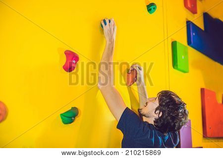 Man Climber On Artificial Climbing Wall In Bouldering Gym