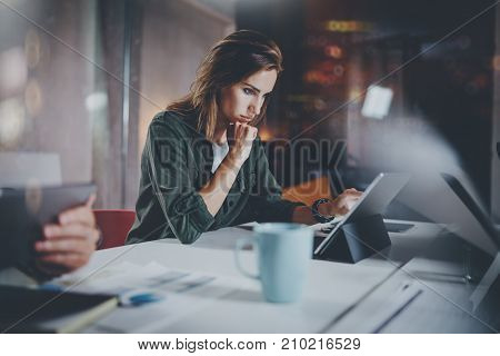 Coworkers working process photo.Young woman working together with colleagues at night modern office loft.Teamwork concept.Blurred background.Horizontal