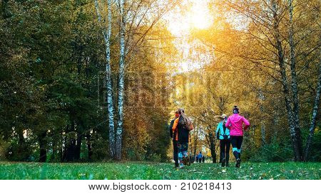 Running athletes park on a run early morning. Several children are running woods doing sports. Healthy lifestyle. Beautiful forest, girls run park autumn.