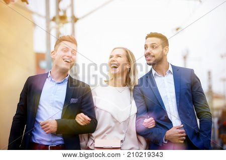 two men and one woman walking and laughing