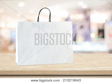 White shopping bag on wooden table over blurred store background business template retail sale product display montage