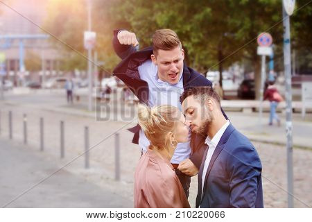 young couple kissing on street while a man is attacking them