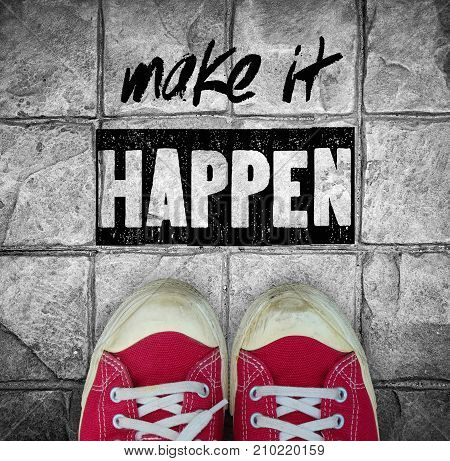Make it happen : inspiration quotation over red canvas sneaker on pavement backgound