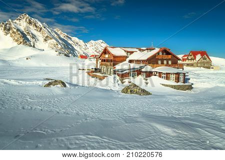 Stunning winter landscape in Fagaras mountains with famous frozen Balea lake and wooden houses Carpathians Transylvania Romania Europe