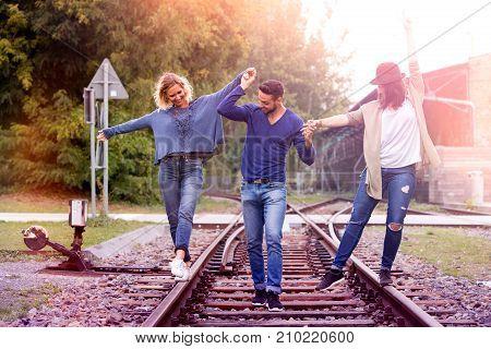 three friends walking on train tracks and having fun