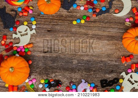 Trick and treat - colorful halloween frame on aged wood with copy space on wooden background