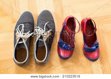 Two pairs of worn shoes of a young couple on the floor.